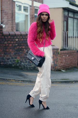 Cómo combinar: jersey corto de angora rosa, pantalón de pinzas en beige, sandalias de tacón de ante negras, bolso bandolera de cuero acolchado negro