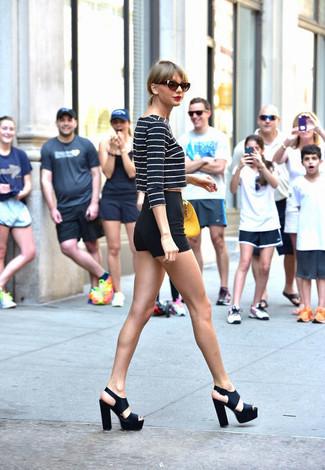 Look de Taylor Swift: Jersey Corto de Rayas Horizontales en Azul Marino y Blanco, Pantalones Cortos Negros, Sandalias de Tacón de Cuero Gruesas Negras, Cartera de Cuero Amarilla