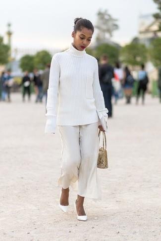 Cómo combinar: jersey de cuello alto de punto blanco, pantalones anchos blancos, zapatos de tacón de cuero blancos, cartera de cuero con print de serpiente en beige
