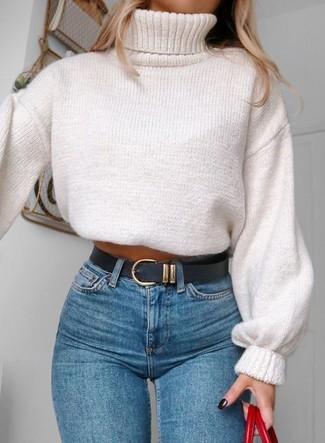 Cómo combinar: jersey de cuello alto de punto blanco, vaqueros pitillo azules, bolsa tote de cuero roja, correa de cuero negra