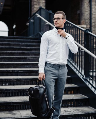 Cómo combinar: jersey de cuello alto azul marino, camisa de manga larga blanca, pantalón de vestir gris, mochila de cuero negra