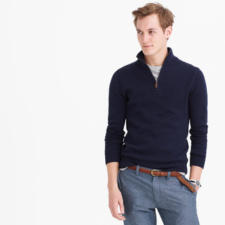 Emparejar un jersey de cuello alto con cremallera azul marino junto a un pantalón de vestir azul es una opción práctica para una apariencia clásica y refinada.