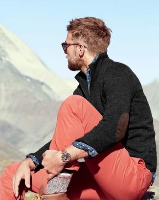 Cómo combinar: jersey de cuello alto con cremallera en gris oscuro, camisa vaquera a lunares azul, pantalón chino rosado, botas de trabajo de cuero marrónes