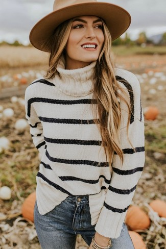 Cómo combinar: jersey de cuello alto de rayas horizontales en blanco y negro, vaqueros pitillo azules, sombrero de lana marrón claro