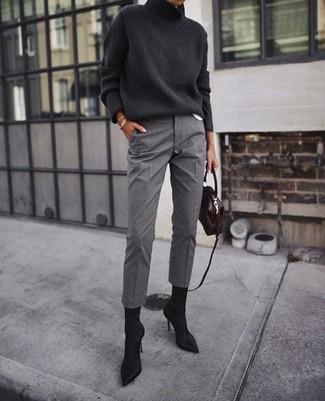 Cómo combinar: jersey de cuello alto de punto en gris oscuro, pantalón de vestir gris, botines de ante negros, bolso bandolera de cuero en marrón oscuro