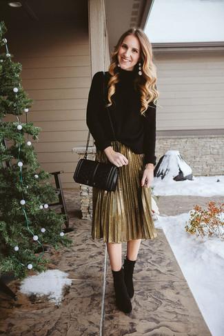 Cómo combinar: jersey de cuello alto de punto negro, falda midi plisada dorada, botines de ante negros, bolso bandolera de cuero acolchado negro