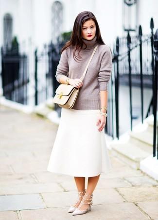 Cómo combinar un bolso bandolera de cuero en beige: Para un atuendo tan cómodo como tu sillón equípate un jersey de cuello alto gris junto a un bolso bandolera de cuero en beige. Zapatos de tacón de cuero con tachuelas grises son una opción perfecta para complementar tu atuendo.