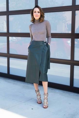 Cómo combinar: jersey de cuello alto gris, falda lápiz de cuero verde oscuro, sandalias de tacón de cuero con print de serpiente grises