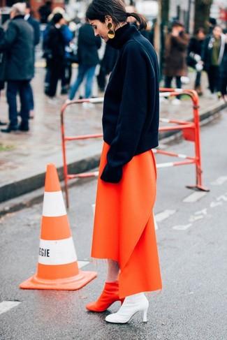 Cómo combinar: jersey de cuello alto de lana negro, falda midi naranja, botines de cuero naranjas, pendientes dorados