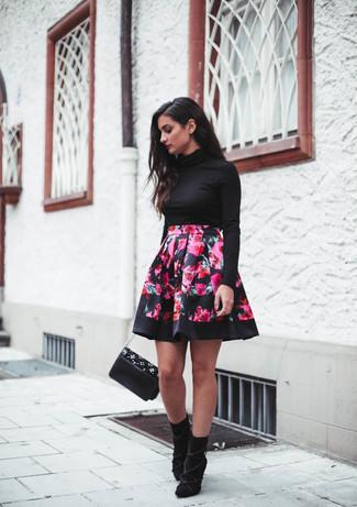Cómo combinar: jersey de cuello alto negro, falda skater con print de flores rosa, botines de ante negros, bolso bandolera de cuero con adornos negro