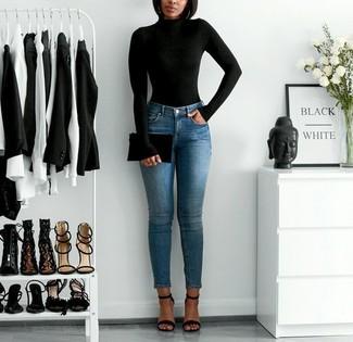 Cómo combinar: jersey de cuello alto negro, vaqueros pitillo azules, sandalias de tacón de cuero negras, cartera sobre de cuero negra