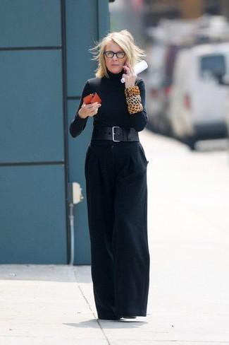 Moda para mujeres de 60 años: Destaca entre otros civiles elegantes con un jersey de cuello alto negro y unos pantalones anchos negros. Este atuendo se complementa perfectamente con botines de cuero negros.