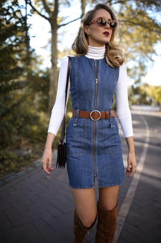 Cómo combinar: jersey de cuello alto blanco, pichi vaquero azul, botas sobre la rodilla de ante marrónes, bolso bandolera de cuero negro