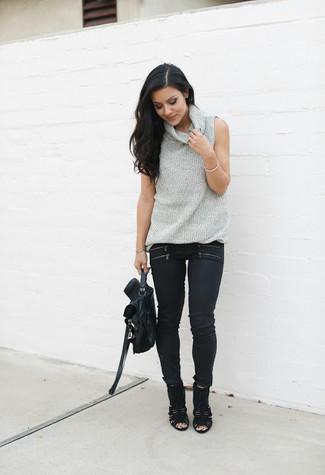 Cómo combinar: jersey de cuello alto sin mangas gris, vaqueros pitillo negros, botines de ante con recorte negros, bolso de hombre de cuero negro