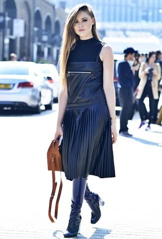 Cómo combinar: jersey de cuello alto sin mangas negro, pichi de cuero negro, botas de caña alta de cuero azul marino, bolsa tote de cuero marrón