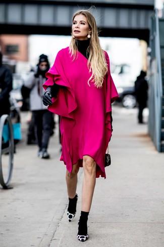 Cómo combinar: jersey de cuello alto negro, vestido recto con volante rosa, zapatos de tacón de ante a lunares en blanco y negro, cartera de cuero negra
