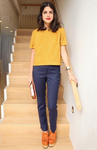 Cómo combinar: jersey de manga corta amarillo, pantalón de vestir azul marino, zapatos de tacón con borlas de cuero naranjas