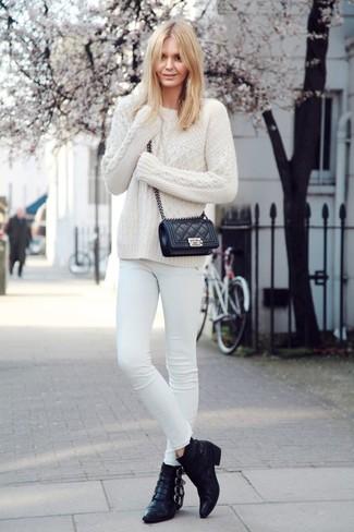 Cómo combinar: jersey de ochos blanco, vaqueros pitillo blancos, botines de cuero negros, bolso bandolera de cuero acolchado negro