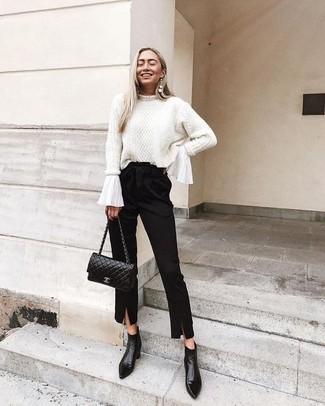 Cómo combinar: jersey de ochos blanco, blusa de manga larga con volante blanca, pantalón de pinzas negro, botines de cuero negros