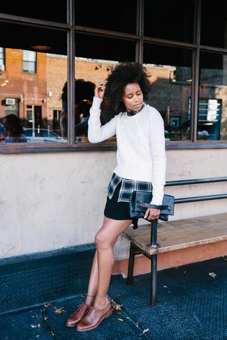 Cómo combinar: jersey de ochos blanco, camisa de vestir de tartán negra, minifalda negra, zapatos brogue de cuero marrónes
