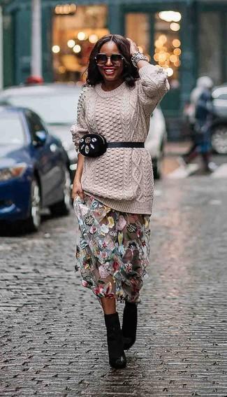 Cómo combinar: jersey de ochos en beige, falda larga de tul con print de flores gris, botines de cuero negros, riñonera de ante negra