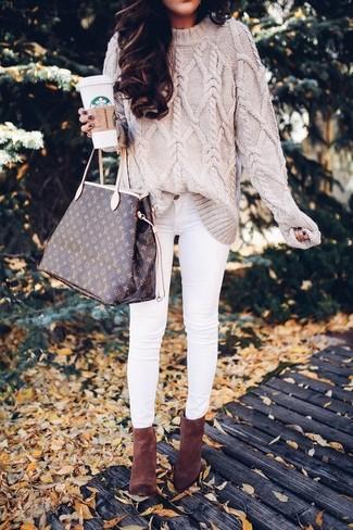 Cómo combinar: jersey de ochos en beige, vaqueros pitillo blancos, botines de ante marrónes, bolsa tote de cuero estampada en marrón oscuro