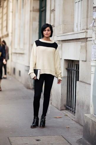 Cómo combinar: jersey de ochos en blanco y negro, vaqueros pitillo negros, botines de cuero negros, cartera sobre de cuero en negro y blanco