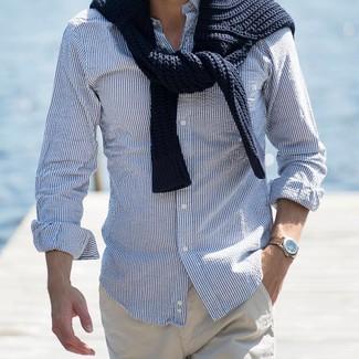 Cómo combinar: jersey de ochos negro, camisa de manga larga de rayas verticales en blanco y azul, pantalón chino en beige