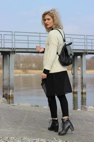 Cómo combinar: jersey de ochos en beige, túnica de gasa negra, vaqueros pitillo negros, botines con cordones de cuero negros