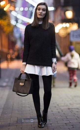 Cómo combinar: jersey de ochos negro, vestido camisa blanca, botines de cuero negros, bolso de hombre de cuero negro