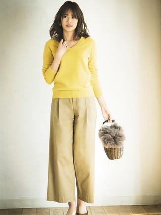 Cómo combinar: jersey de pico amarillo, pantalones anchos marrón claro, zapatos de tacón de ante marrónes, cartera de paja marrón claro