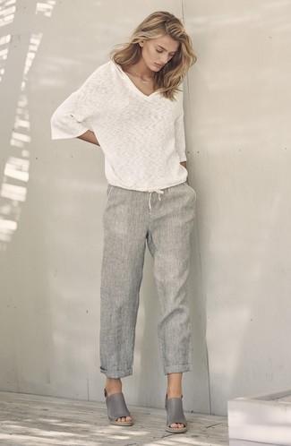 Cómo combinar: jersey de pico blanco, pantalones anchos de lino grises, sandalias con cuña de cuero grises