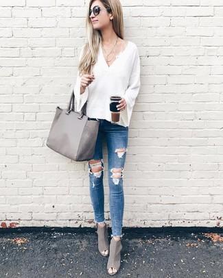 Cómo combinar: jersey de pico blanco, vaqueros pitillo desgastados azules, botines de cuero con recorte grises, bolsa tote de cuero gris