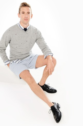 Cómo combinar: jersey de pico gris, camisa de manga larga de rayas horizontales en blanco y azul, pantalones cortos de seersucker de rayas verticales celestes, zapatos brogue de cuero negros