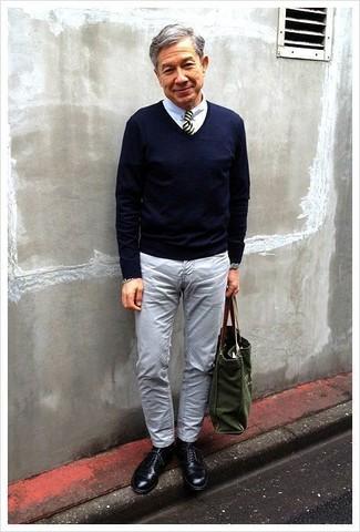 Cómo combinar: jersey de pico azul marino, camisa de vestir blanca, vaqueros grises, zapatos derby de cuero negros