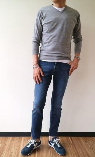 Casa un jersey de pico gris junto a unos vaqueros pitillo azul marino para conseguir una apariencia relajada pero elegante. Tenis de ante azul marino son una sencilla forma de complementar tu atuendo.