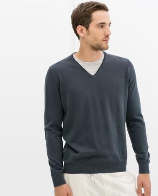 Emparejar un jersey de pico en gris oscuro y un pantalón de chándal blanco es una opción cómoda para hacer diligencias en la ciudad.