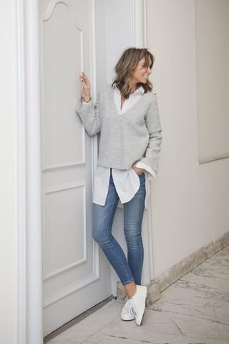 Utiliza un jersey de pico gris y unos vaqueros pitillo azules para una apariencia fácil de vestir para todos los días. ¿Por qué no añadir tenis de lona blancos a la combinación para dar una sensación más relajada?
