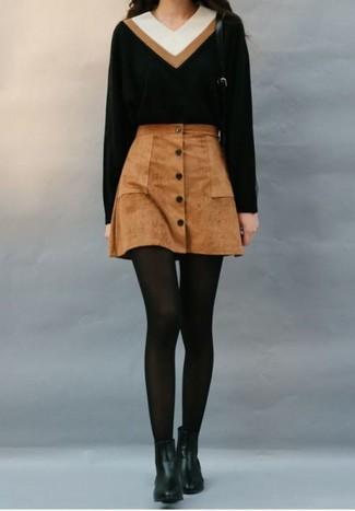 Cómo combinar: jersey de pico negro, falda con botones de ante marrón, botines chelsea de cuero negros, medias de lana negras