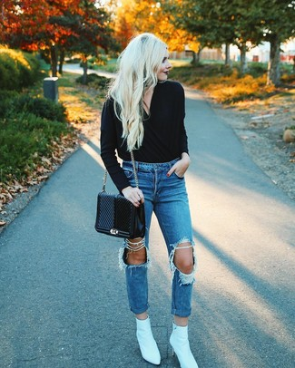 Cómo combinar: jersey de pico negro, vaqueros boyfriend desgastados azules, botines de cuero blancos, bolso de hombre de cuero acolchado negro