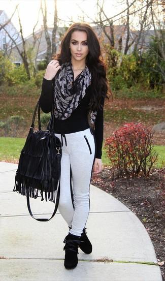 Cómo combinar: jersey de pico negro, pantalón de chándal en blanco y negro, zapatillas altas de ante negras, bolsa tote de cuero сon flecos negra