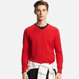 Intenta combinar un jersey de pico rojo con un pantalón chino negro para un almuerzo en domingo con amigos.