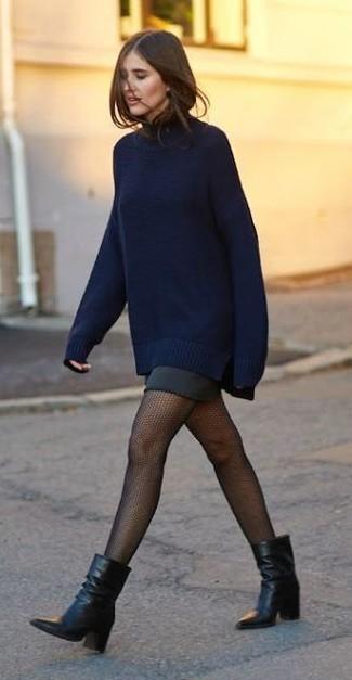 Cómo combinar: jersey oversized azul marino, minifalda negra, botines de cuero negros, medias de red negras