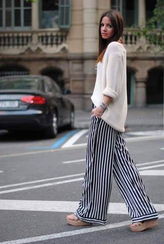 Cómo combinar: jersey oversized de punto blanco, pantalones anchos de rayas verticales en blanco y negro, sandalias tejidas marrón claro, pulsera azul