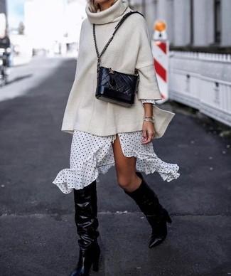 Cómo combinar: jersey oversized de punto en beige, vestido cruzado a lunares en blanco y negro, botas de caña alta de cuero negras, bolso bandolera de cuero acolchado negro