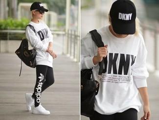 Cómo combinar: jersey oversized estampado blanco, leggings estampados negros, tenis blancos, bolsa tote de cuero negra