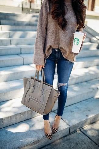 Cómo combinar: jersey oversized marrón, vaqueros pitillo desgastados azules, zapatos de tacón de ante de leopardo marrónes, bolsa tote de cuero gris
