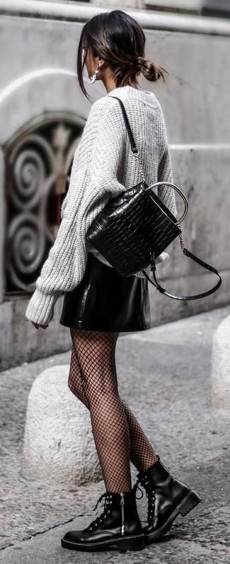 Cómo combinar: jersey oversized de punto gris, minifalda de cuero negra, botas planas con cordones de cuero negras, mochila de cuero acolchada negra