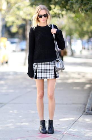 Cómo combinar: jersey oversized negro, minifalda de tartán en negro y blanco, botas planas con cordones de cuero negras, bolso bandolera de cuero plateado