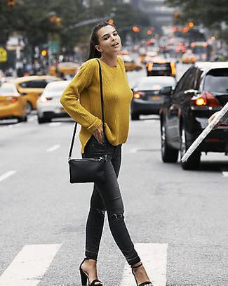 Cómo combinar: jersey oversized mostaza, vaqueros pitillo desgastados negros, sandalias de tacón de ante negras, bolso bandolera de cuero negro